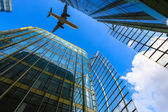 Airliner and modern glass building — Stock Photo