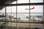 Window of the airport with flight arrival — Stock Photo