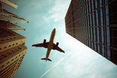 Airplane and modern building — Stock Photo