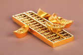 Gold ingots and abacus — Stock Photo