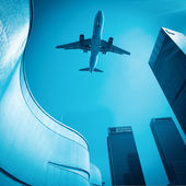 Airplane and modern buildings — Stock Photo