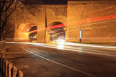 Light trails through the ancient city wall at night — Stock Photo