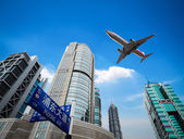 Upward view airplane with modern building — Stock Photo