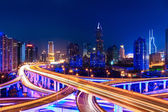 Modern city skyline with interchange overpass at night — Stock Photo