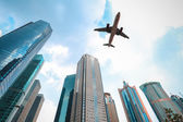 Modern buildings with airplane — Stock Photo