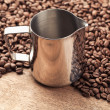 Coffee pitcher and beans on old wooden table — Stok fotoğraf