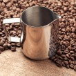 Coffee pitcher and beans on old wooden table — Stock Photo