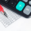 Calculator and red pen — Stock Photo