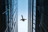 Glass skyscraper and airplane — Stock Photo