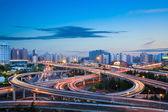 Modern city interchange overpass in nightfall  — Stok fotoğraf