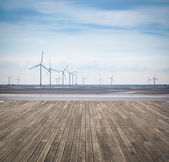 Wind farm in mud flat with wooden floor — Stock Photo