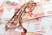 Heap soft money and old spectacles — Stock Photo