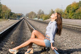Beautiful girl sitting on rails — Stockfoto