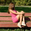 Stock Photo: Girl sitting on bench in autumn park