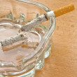 Cigarette in a glass ashtray — Stock Photo