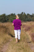 Woman is walking on heath — Stock Photo