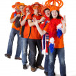 Stock Photo: Group of Dutch soccer fans making polonaise over white backgroun