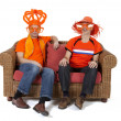 Two Dutch soccer fan watching game over white background — Stock Photo