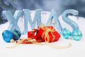 The word Xmas in blue glitter letters with balls and presents — Stok fotoğraf