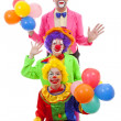 Three people dressed up as colorful funny clowns over white back — Stock Photo #43148647