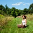 Young woman meditating in nature — Stock Photo