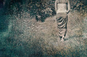 Young woman walking away in nature — Stock Photo