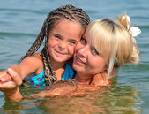 Mother with daughter on beach — Stock Photo