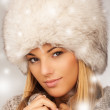 Portrait of young beautiful female wearing winter clothing and fur hat winter clothes, very warm and thickly clothed. — Stock Photo #41289335