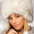Portrait of young beautiful female wearing winter clothing and fur hat winter clothes, very warm and thickly clothed. — Stock Photo #41289337