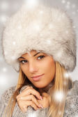 Portrait of young beautiful female wearing winter clothing and fur hat winter clothes, very warm and thickly clothed. — Stock Photo