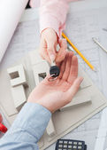 Female architect handing over the keys of finished project - new house — Stock Photo