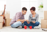 Couple in apartment looking into tablet — Stock Photo