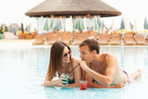 Happy couple having cocktails in the pool — Stock Photo