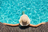 Woman with big hat relaxing on the swimming pool — 图库照片