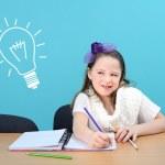 Smiling girl doing her school work — Stock Photo