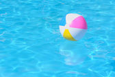 Inflatable multy colored plastic ball in swimming pool — Stock Photo
