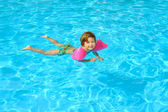 Toddler girl learning to swimm in the swimming pool — Stock Photo