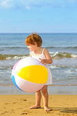 Toddler girl playing with her inflatable ball at beach — Stock Photo