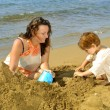 Mother and her daughter playing with toys and sand at beach — Stock Photo