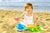 Happy toddler girl playing with her toys at beach — Stock Photo