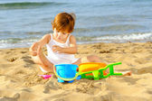 Happy toddler girl playing with her toys on the beach — Stock Photo