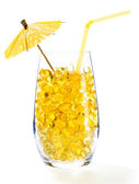 Healthy vitamin cocktail: yellow oil pills in translucent glass — Zdjęcie stockowe