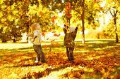 Niños jugando con hojarasca otoñal en el parque — Foto de Stock