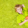 Child lying on the green carpet background, holding apple. Boy s — Stock Photo #13406247