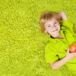 Child lying on the green carpet background, holding apple. Boy s — Stock Photo