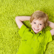 Happy child lying on the green carpet background. Boy smiling an — Stock Photo