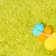 Knitting yarn balls and needles over green carpet background — Stock Photo