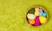 Knitting yarn balls and needles in basket over green carpet back — Stock Photo