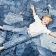 Happy child on jeans background. Denim fashion — Stock Photo