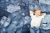 Happy child on jeans background. Denim fashion — Photo